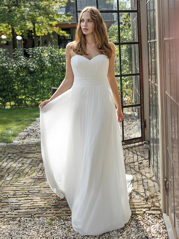 Woman walking in a Curves By Modeca wedding dress