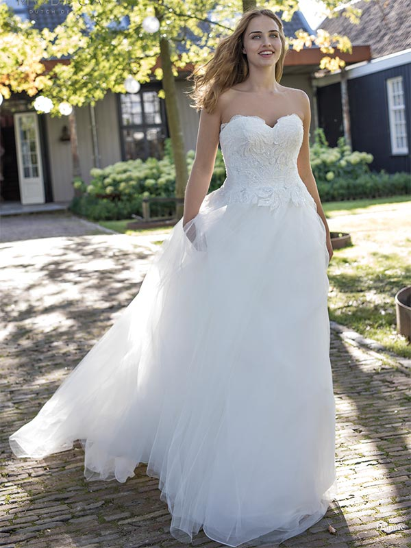Woman in a garden wearing a Curves By Modeca wedding dress