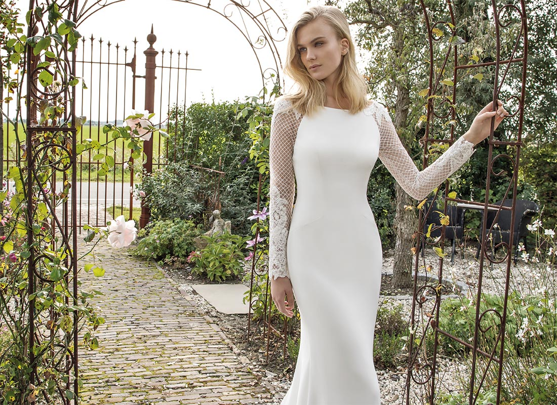 Woman in front of garden gate wearing a Modeca Bridal dress