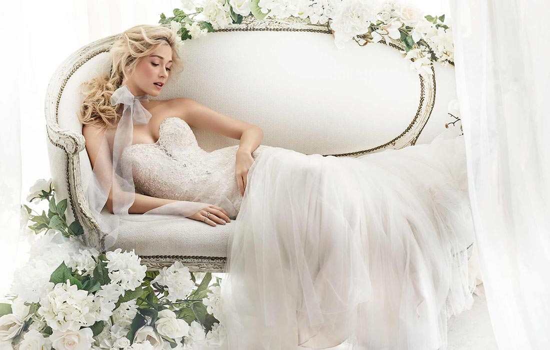 Bride lying gracefully on a white couch wearing an Ella Rosa wedding dress