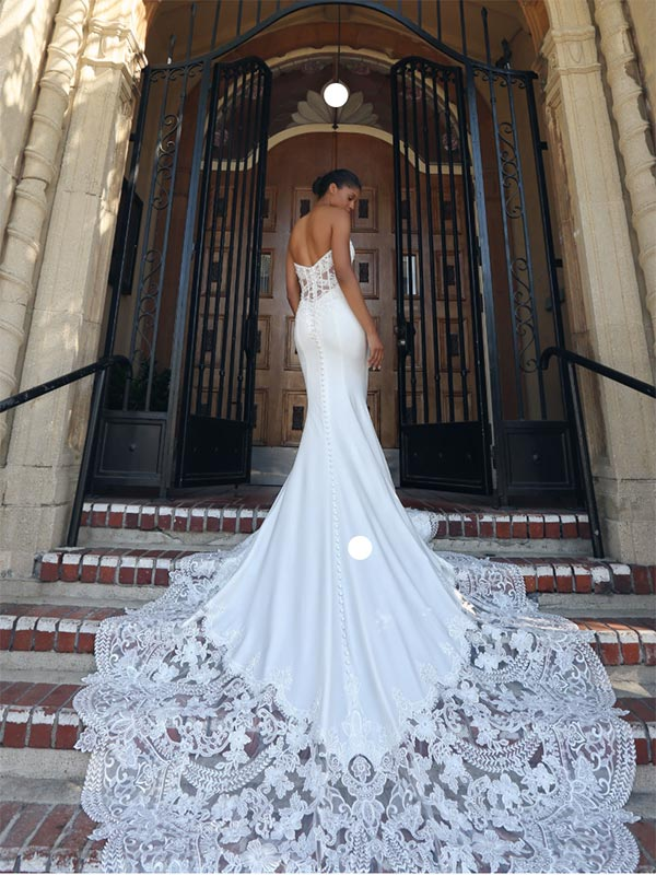 Bride standing on steps wearing a Kenneth Winston wedding dress